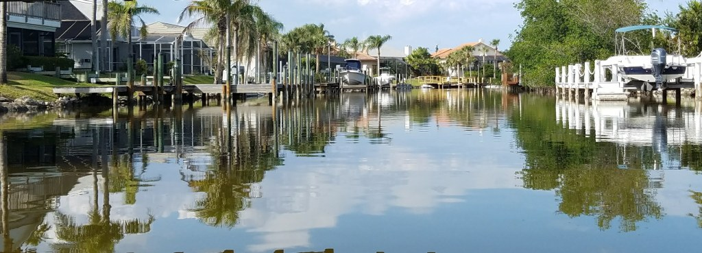 Kayakers view of the Grand Canal. Their are boat docks & boats on either side of the waterway. There is a reflection of the sky, clouds, & palm trees on the glassy water.