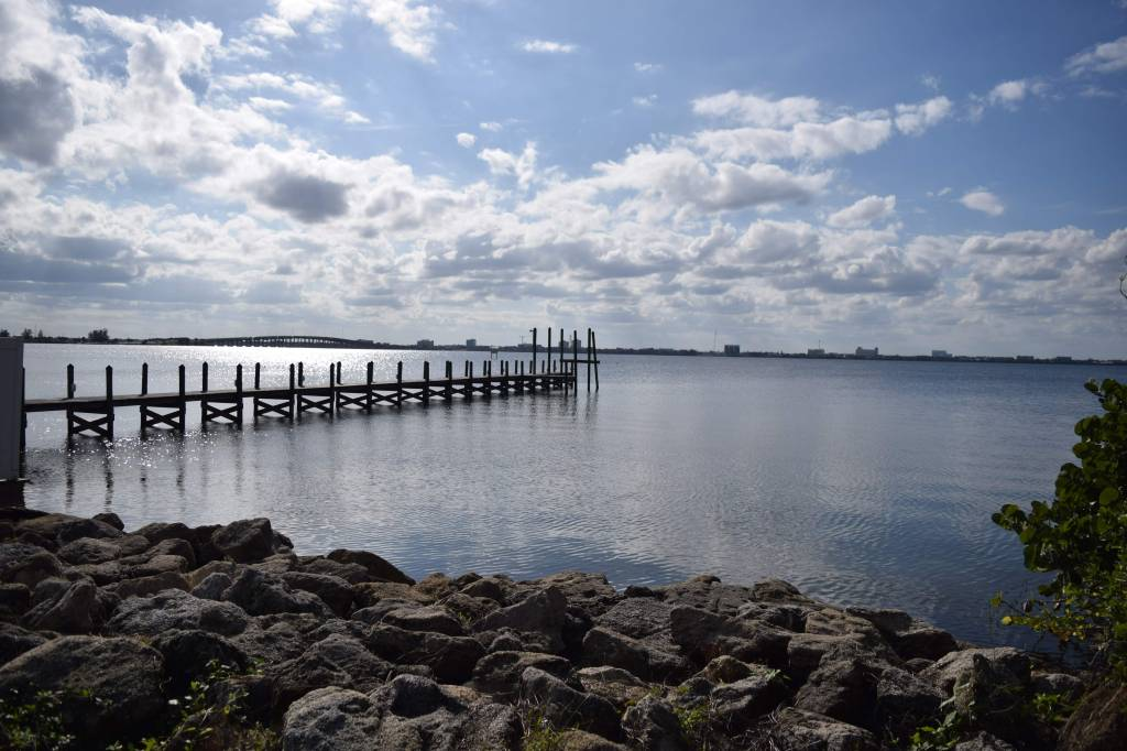 Mid afternoon view of the Indian River from Indialantic Florida. Rocks line the shoreline in the photo with a dock stretching out into the intracoastal river. In the distance is the Melbourne Causeway.